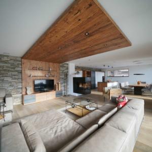 Wohnzimmer mit Holzdecke, Steinwand, Kachelofen drehbar