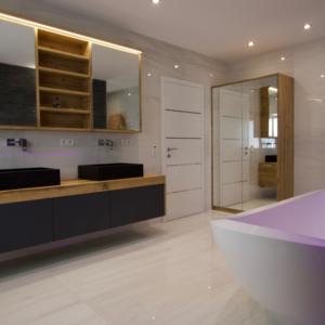 Badezimmer mit dunklen Fronten, Spiegelschrank, Waschtisch mit schwarzen Aufsatzbecken, moderne Badewanne