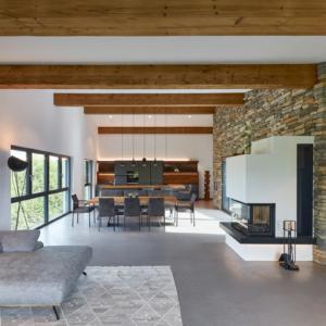 Wohnzimmer mit Steinwand, moderner Kachelofen, Holzwand mir Beleuchtung, Tramdecke Eiche, Altholz