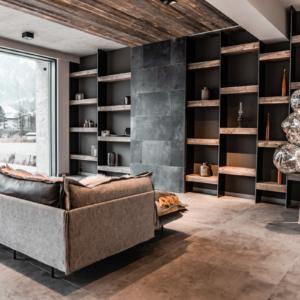 Wohnzimmer mit Regal in Altholz, Lederschiebetüre, versteckter Fernseher, Stehleuchte Tom Dixon, Decke in Altholz grau