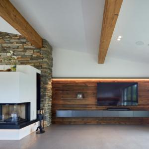 modernes Wohnzimmer mit Wandverkleidung , Sideboard in Eisen, Eisenfächer, moderner Kachelofen