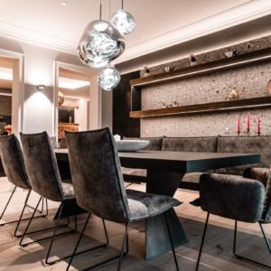Essplatz mit massivem Esstisch, Tischplatte geköhlt, Stühle und Bank Vintage Leder, Wand in Konglomerat, Wandboard mit LED Beleuchtung, Parkett Eiche weiß geölt, Hängelampe Tom Dixon