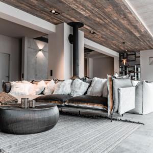 Innenarchitektur mit Altholzdecke, Artemide Couch mit Fellkissen, Betondecke, grauer Teppich, Wohnzimmertisch Lambert in Eisen