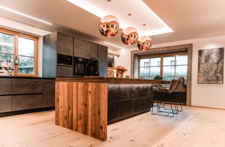 Moderne Küche mit Altholz und Insel mit Lederverkleidung