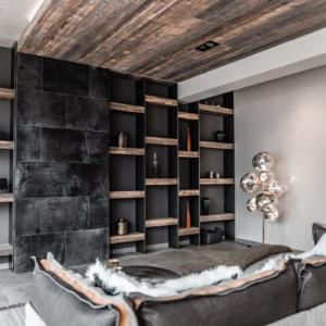 Wohnzimmer mit Regal in Altholz, graue Wand, Lederschiebetüre, versteckter Fernseher, Stehleuchte Tom Dixon, Decke in Altholz grau