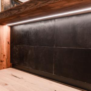Kochinsel mit Altholz und Lederfronten, Hochschränke in Beton, schwarze Armatur, Bora Kochfeld, Leuchten ™ Dixon, Barhocker KFF Vintage Leder