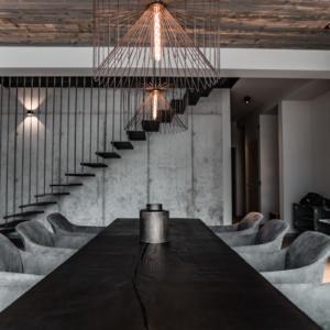 Betonwand, Eisentreppe, Tisch geköhlt, Regal mit Altholz und Eisen, Drahtlampen
