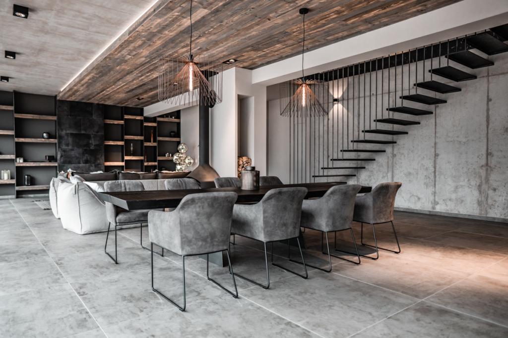 Wohnzimmer modern, Altholzdecke in grau, Esstisch massiv geköhlt, Regalwand mit Leder und Holz, Stiegenaufgang im Wohnzimmer