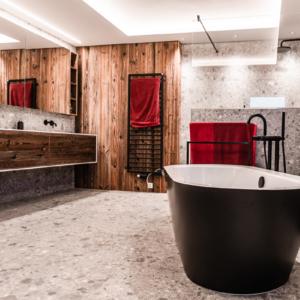 Waschtisch in weiß, Badewanne schwarz,Badezimmer in Altholz, Keramikfliesen grau gemustert, Armatur in schwarz, Altholzwand, Handtuchhalter in schwarz
