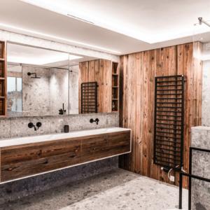 Waschtisch in weiß, Badezimmer in Altholz, Keramikfliesen grau gemustert, Armatur in schwarz, Altholzwand, Handtuchhalter in schwarz