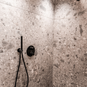 Waschtisch in weiß, Badezimmer in Altholz, Keramikfliesen grau gemustert, Armatur in schwarz