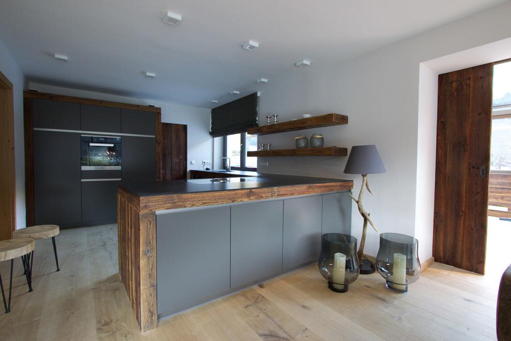 graue Küchenfronten, modernes Küchendesign mit Altholz und Granit, Altholzregale
