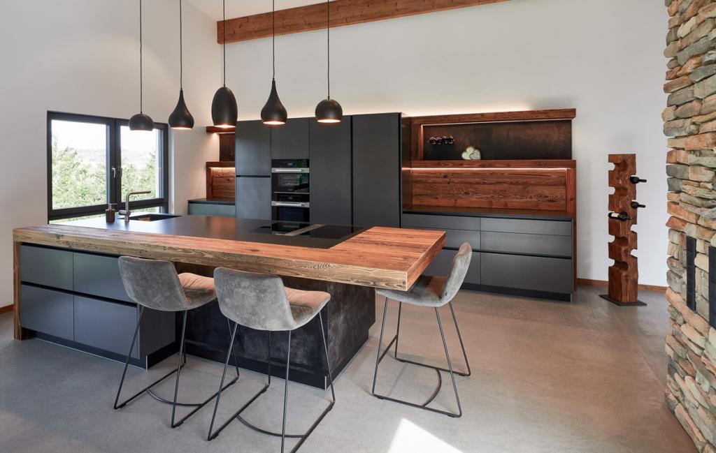 dunkle Küche mit Holz, Kücheninsel mit Leder und Ansatztisch, Rückwand in Holz mit Nischenschrank, Küchenbeleuchtung mit LED