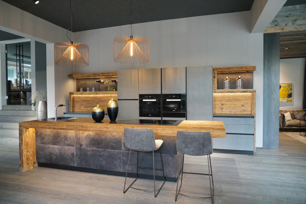 Küchenstudio Sendlhofer, graue Küche mir Altholz und Lederfronten, Kochinsel mit Ansatztisch und Bar in Holz