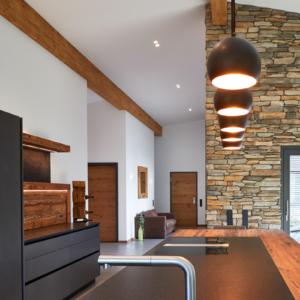 Kücheninsel mit schwarzer Granitplatte, schwarze Spüle, Bora Kochfeld, Küchenbeleuchtung, Steinwand